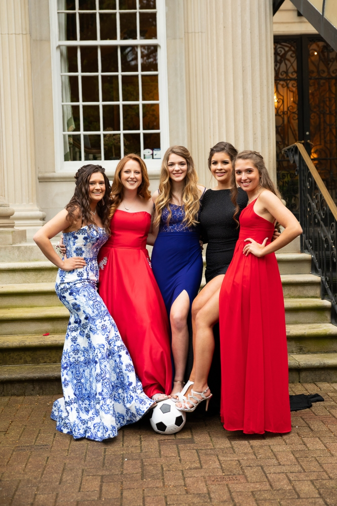 fredrick douglass high school prom, group of 5 girls in prom dresses with feet touching soccer ball. Prom photos taken at Spindletop Hall in Lexington, KY