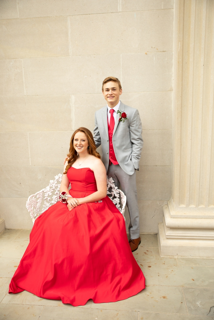 prom dates, girl in red dress seated with her date in gray suit standing behind her. Photo taken at Spindletop Hall in Lexington, KY