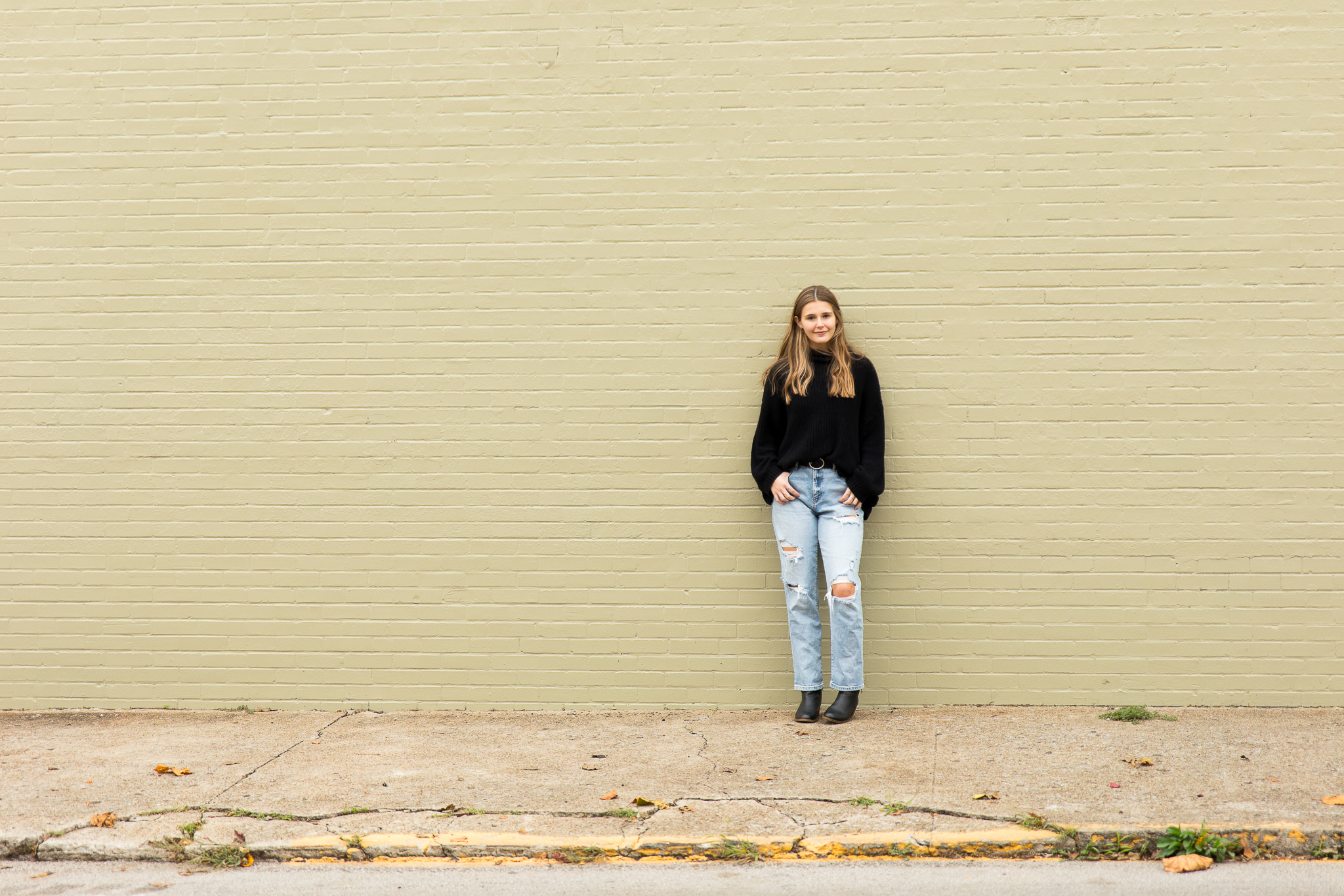 lexington ky high school senior portrait of girl with long bronw hair in black sweater standing in front of a painted brick wall